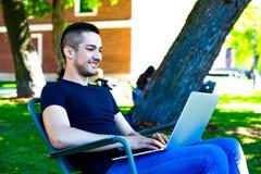 Junger lächelnder MannStudent, der on-line-Ausbildung über das tragbare Notizbuch, stehend auf einem Campus hat still stockbild