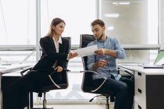 Junger lächelnder persönlicher Assistent, der dem Büroangestellten in seinem Büro Dokument, weiblicher Buchhalter berichtet große lizenzfreie stockfotos