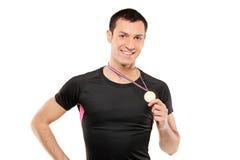 Junger lächelnder Sportler, der eine Goldmedaille anhält Stockbilder