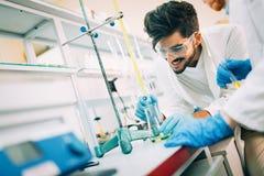 Junger lächelnder Student im weißen Mantel, der chemische Aufgaben tut lizenzfreies stockbild
