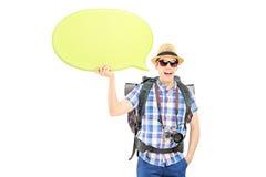 Junger lächelnder Wanderer, der eine leere Spracheblase hält Stockfotografie