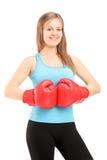 Junger lächelnder weiblicher Athlet, der rote Boxhandschuhe und posin trägt Lizenzfreies Stockfoto