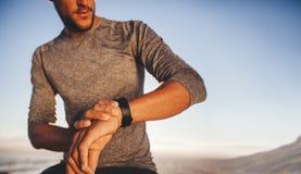 Junger Läufer, der die Zeit auf seiner Armbanduhr überprüft Stockbild