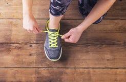 Junger Läufer, der ihre Schuhe bindet Stockbilder