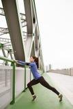 Junger Läufer in der Stadt, die auf grüne Stahlbrücke ausdehnt Stockbild