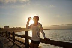 Junger Läufer, der von einer Wasserflasche trinkt Lizenzfreies Stockbild
