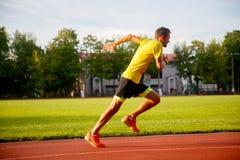 Junger Läufer lässt Stadionssommer laufen Stockbild