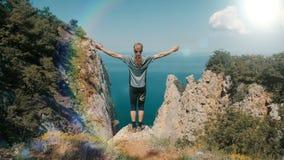 Junger langhaariger angespornter Mann hebt seine Hände herauf die Stellung auf die Oberseite eines Berges über dem Meer gegen sch stock video