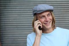 Junger langhaariger blonder Mann, der draußen am Handy mit Kopienraum auf dem links lächelt und spricht Stockfotografie