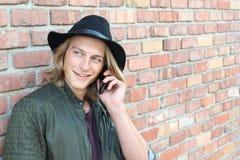 Junger langhaariger blonder Mann, der draußen am Handy mit Raum für Kopie lächelt und spricht Stockfoto