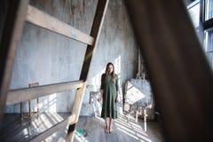 Junger langhaariger Frauenmaler in einem grünen Kleid mit einer Bürste und in einer Palette in einem Kunststudio stockfotografie
