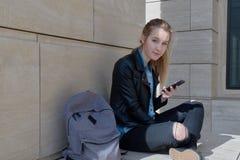 Junger langhaariger FrauenStudentinreisender in den schwarzen Jeans und ein Lederjackesitzen im Schneidersitz mit einem Smartphon lizenzfreies stockbild