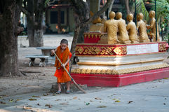 Junger laotianischer Mönch räumt Bottich Phiavat-Kloster nach religiöser Feier auf. Lizenzfreies Stockfoto