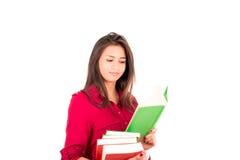 Junger lateinischer Mädchen-Holdingstapel Bücher und Lesung stockbilder