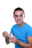 Junger Latino, der einen Joghurt isst Lizenzfreie Stockfotografie