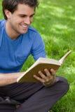 Junger lächelnder Mann, der ein Buch beim Stationieren auf dem Gras liest Stockbild