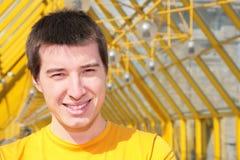Junger lächelnder Mann im gelben Hemd Stockfotografie