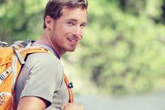 Junger lächelnder Rucksackmann in der Sommerwaldnatur Lizenzfreies Stockbild