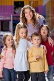 Junger Lehrer-With Children In-Kindergarten stockfoto
