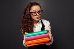 Junger Lehrer in den Gläsern, die Bücher anbieten Stockfotos