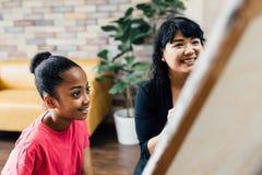 Junger Lehrer, der Afroamerikanerkind eine Kunstlektion gibt und wie man auf Gestell innerhalb des Wohnzimmers unterrichtet, malt lizenzfreies stockbild