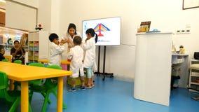 Junger Lehrer, der chemisches Experiment mit Kindern tut, um Theorie der Vulkanexplosion zu erklären stock footage