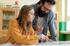 Junger Lehrer, der seinem Studenten im Chemieunterricht hilft getrennte alte Bücher Lizenzfreies Stockbild