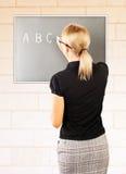 Junger Lehrer schreiben auf Tafel lizenzfreie stockfotos