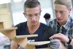 Junger Lehrling in der caprentry Schule mit Lehrer lizenzfreie stockfotos