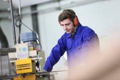 Junger Lehrling, der in der Metallurgiewerkstatt arbeitet Lizenzfreies Stockfoto