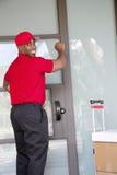 Junger Lieferer mit den Paketen, die zurück beim Klopfen auf Tür schauen Stockfoto