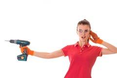 Junger lustiger Brunettefrauenerbauer in der Uniform mit Gläsern und bohren herein ihre Hände machen reovations lokalisiert auf W stockfotografie