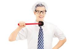 Junger lustiger Mann, der ungefähr eine Toilettenbürste hält, um seine Zähne zu säubern Stockbild