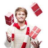 Junger lustiger Mann jonglieren die Weihnachtsgeschenke Lizenzfreie Stockfotos