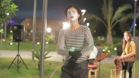 Junger lustiger Pantomime, der herum täuschen im Park aufwirft stock video