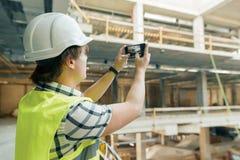 Junger männlicher Architekt fotografiert eine Baustelle Gebäude-, Entwicklungs-, Teamwork- und Leutekonzept lizenzfreies stockfoto