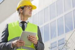 Junger männlicher Architekt mit der digitalen Tablette, die weg äußeres Gebäude schaut Stockbilder