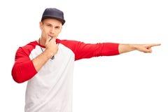 Junger männlicher Baseballreferent, der eine Pfeife durchbrennt Stockfotografie