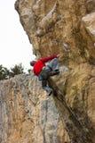 Junger männlicher Bergsteiger, der an einer Klippe hängt Stockfotografie