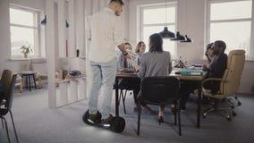 Junger männlicher Chef, der hoverboard verwendet, um mit Kollegen zu kommen und zu sprechen Überzeugter Führer setzt Technologie  stock video footage