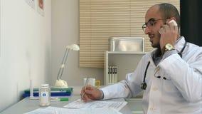 Junger männlicher Doktor in den Gläsern, die einen Telefonanruf entgegennehmen stock footage