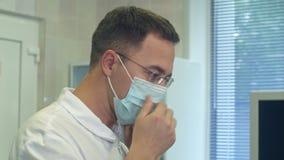 Junger männlicher Doktor, der chirurgischen Hut an in einen Chirurgieraum einsetzt stock video footage
