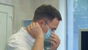 Junger männlicher Doktor, der chirurgischen Hut an in einen Chirurgieraum einsetzt Lizenzfreie Stockfotografie