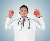Junger männlicher Doktor, der einen roten Apfel hält Lizenzfreie Stockbilder