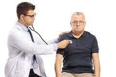 Junger m?nnlicher Doktor, der herauf einen besorgten m?nnlichen Patienten mit einem Stethoskop ?berpr?ft lizenzfreie stockfotografie