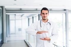 Junger männlicher Doktor, der leere Hände hält Lizenzfreie Stockfotos
