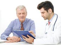 Junger männlicher Doktor mit älterem Patienten Lizenzfreie Stockfotos