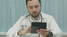 Junger männlicher Doktor mit einem Taschenrechner machen stock footage