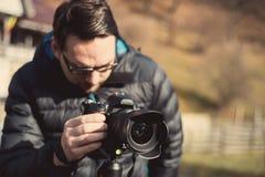 Junger männlicher Fotograf, der die Kamera vorbereitet Lizenzfreies Stockbild