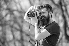 Junger männlicher Fotograf, der Fotos im Park mit Weinlesekamera, Hobby und Freizeitbetätigungskonzept macht bärtig lizenzfreie stockfotos